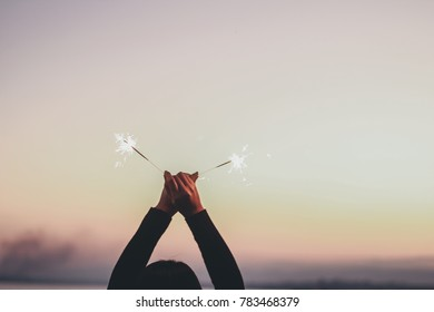 Abstract blur sparklers for celebration background,Motion by wind blurred woman two hand holding burning Christmas sparklers on nature twillight sky background.Winter vintage film grain filter style.