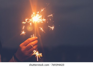 Abstract blur sparklers for celebration background,woman hand holding a burning sparkler light with purple sky background.closeup in female hand in dark. happy holidays.Vintage flim grain Style.
