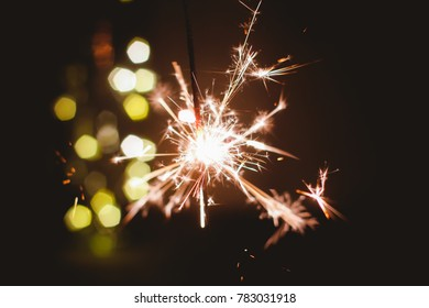 Abstract blur sparklers for celebration christmas,happy new year,party,festival background,Motion Blurred by wind Sparklers with pentagon bokeh background.Winter Dark vintage night  film grain style.