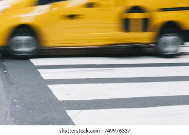 Abstract blur of urban street scene with a yellow taxi cab in New York, United States
