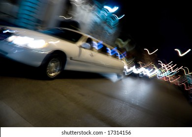 An abstract blur of a white limousine in the city at night with light trails.
