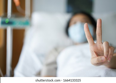 Abstract blur women show two finger and treatment in patient bed with IV tube , Grain