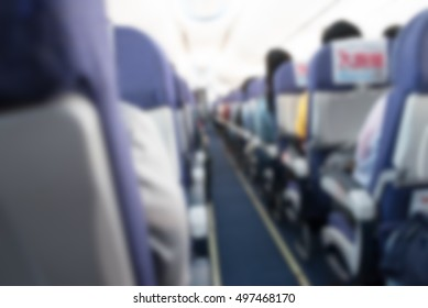 Abstract blurred aircraft cabin view of economy class with passenger background. Travel concept with public aviation transport.