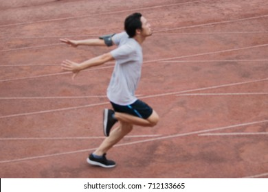 Abstract blurred of athletic handsome young Asian runner sprinter crossing the finish line on track in stadium.