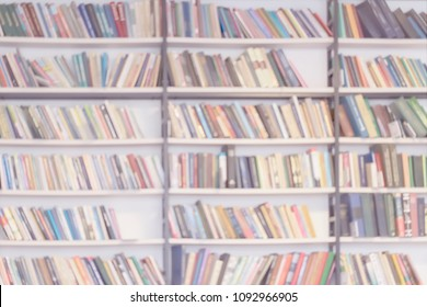 Abstract blurred background of bookshelves with books in public library, book store, at home, modern light background. Concept of learning, back to school, education