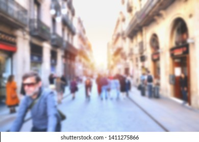 Abstract blurred background image of people walking on a street along buildings in a town in Europe.