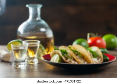 Abstract Blurred Background Of Mexican Food Tacos And Tequila Shots Drinks With Limes For Drinking And Ingredients. Blur Applied. Copy Space.