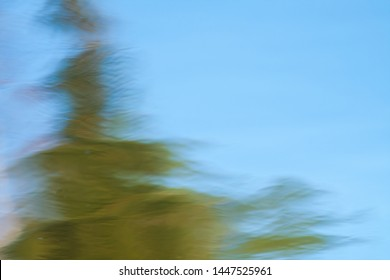 abstract blurred background, reflection of trees on a water surface in a good summer day , Impressionism effect, natural photo