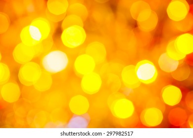 abstract blurred background - yellow and red shimmering Christmas lights bokeh of electric garlands on Xmas tree