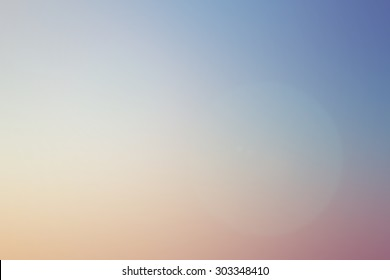 abstract blurred beautiful pastel color of sunset beach with lens flare effect background.