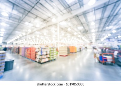 Abstract blurred big boxes wholesale store in America. Wide perspective view of large warehouse with aisles and shelves of products.