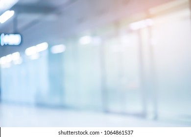 abstract blurred blue color of mirror interior office corridor pathway background concept with orange light filter for design as presentation ads banner concept