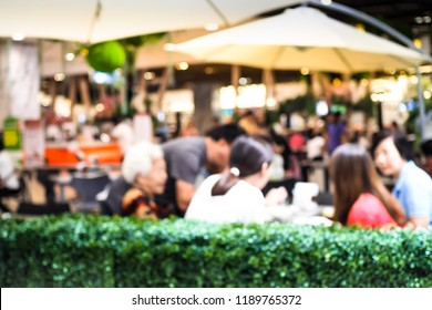 Abstract blurred boken Happy family is enjoying food in restaurant at the shopping mall - vintage style picture.