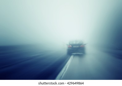 Abstract blurred car high speed driving on wet rainy and foggy highway. Motion blur illustrates the speed and dynamics.