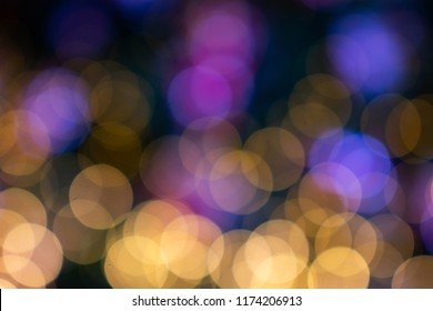 Abstract blurred circular yellow and purple light bokeh with dark background