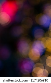 Abstract blurred circular yellow red and purple light bokeh with dark background