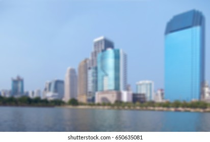 Abstract blurred cityscape with lake and high-rise building.