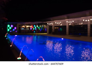 Abstract blurred of colorful lightbulb bokeh around swimming pool at night, can be used for Christmas or new year party background