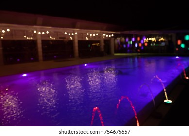 Abstract blurred of colorful lightbulb bokeh around swimming pool with fountain at night, can be used for Christmas or new year party background