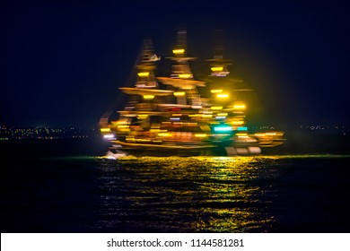 Abstract blurred colorful neon illuminated ship for travels, excursions at night in city close-up. Concept of modern lifestyle, for bright background
