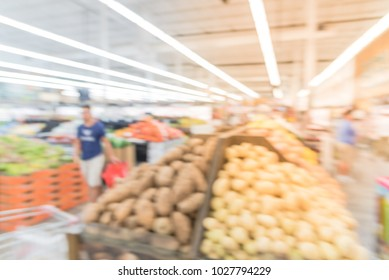 Abstract blurred customers shopping for fresh fruits, vegetable, produces at Asian supermarket. Defocused food background people browsing at grocery store in America.