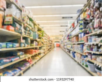 Abstract blurred dog and cat food shelves at American supermarket. Defocused pet supplies, laundry, dish soap, cat litter, pet and home care aisle row display with price tags.