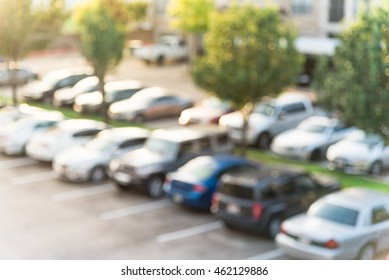 Abstract blurred elevated view of apartment garage with full of covered parking, cars and green trees at multi-floor residential buildings in Houston, Texas, US. Aerial view of crowded parking lot.