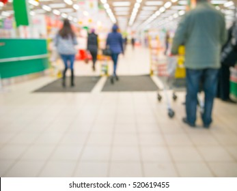 Abstract blurred entrance area of supermarket with unrecognizable customers as background