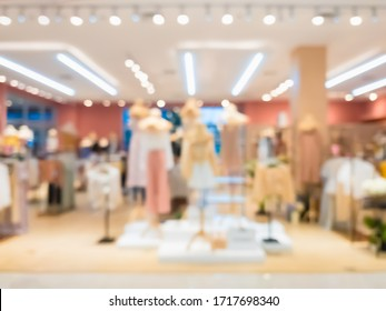 Abstract blurred of fashion clothes shop boutique interior in shopping mall, with bokeh light background. Blurred image of mannequins inside a women fashion store.