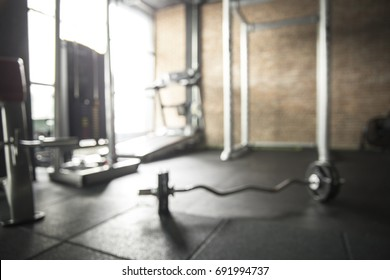 Abstract of Blurred fitness gym with barbell equipment for weight training and treadmill.Bright tone in a room
