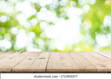 abstract blurred garden and green leaf with wooden table counter background for show , promote ,design on display concept