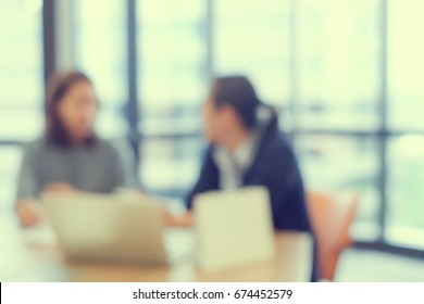 abstract blurred group of two business woman talking,discussion about her work in office meeting room,blurry people background concept,vintage color effect