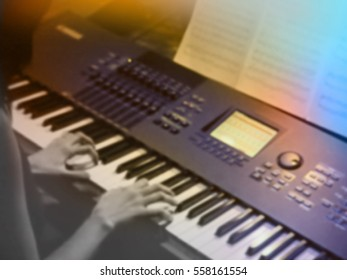 abstract blurred image. Actor playing on the keyboard synthesizer piano keys. Musician plays a musical instrument on the concert stage.