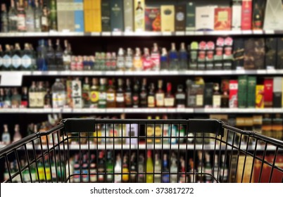 Abstract blurred image of alcohol store with trolley in department store. (Selective focused at shopping cart)