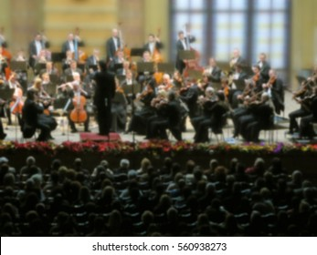 abstract blurred image. Artists symphony orchestra. Musician plays a musical instrument on the concert stage.