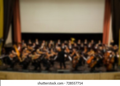 abstract blurred image. Artists symphony orchestra. Musician plays a musical instrument on the concert stage. Background for design, blur texture, actors on stage scene in concert.