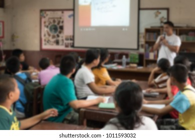 Abstract blurred image of classroom teacher and students.