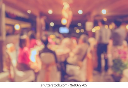 Abstract blurred image of Large dining table set for wedding, dinner or festival event with beautiful lights decoration inside large hall for background usage . (vintage tone)