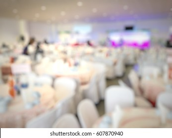 Abstract blurred image of Large dining table set for party, dinner or festival event with beautiful lights decoration inside large hall for background usage