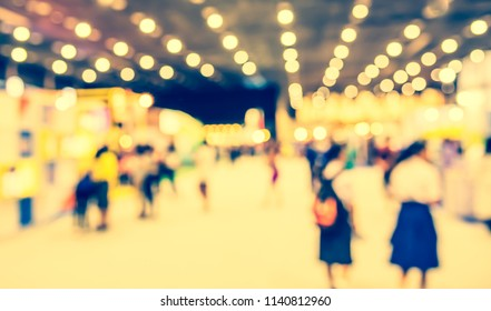 Abstract Blurred image of People walking at Exhibition hall with bokeh for background usage. (vintage tone)