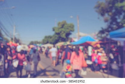 Abstract Blurred image of people walking at day market on street for background usage . (vintage tone)
