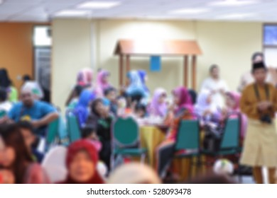 Abstract blurred image of unknown people attend for wedding, dinner or festival event with beautiful lights decoration inside large hall for background usage