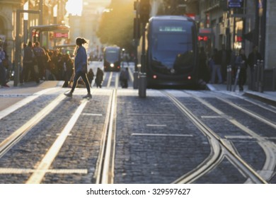Abstract blurred image of woman cross the street in Bordeaux city at sunset, France