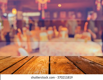 Abstract blurred image of wood table and Large dining table set for wedding, dinner or festival event with beautiful lights decoration inside large hall for background usage . (vintage tone)