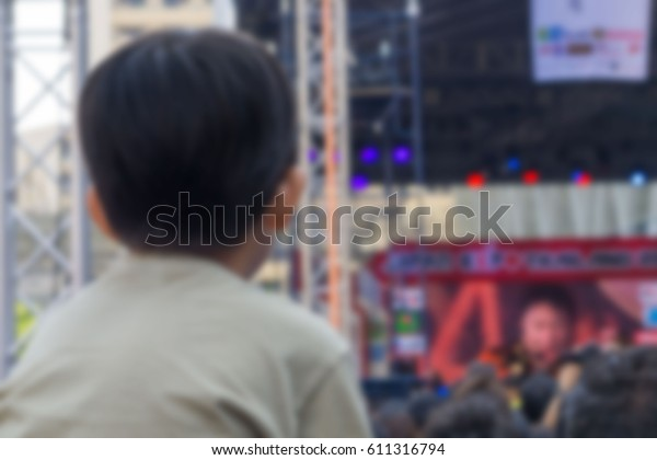Abstract blurred  . A kid sitting on the shoulders of his father at outdoor concert