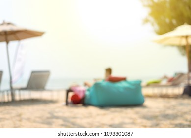 abstract blurred of man sitting on bean bags at the beach - Summer Time