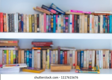 Abstract blurred modern white bookshelves with books, manuals and textbooks on bookshelves in library or in book store, for backdrop. Concept for education.