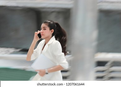 Abstract blurred motion of young Asian business woman running to work.
