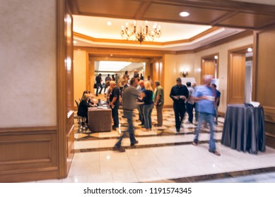 Abstract blurred participants queue line and check-in at registration table of business workshop in America. Multiethnic people sign-up and received instruction, event package from support staff