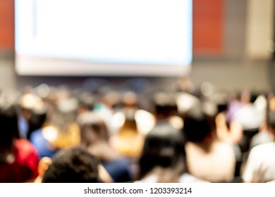 Abstract blurred of people attendee attention listening and lecture in conference hall or seminar room in Exhibition Center, Bokeh business meeting conference,  learning coaching or training concept.